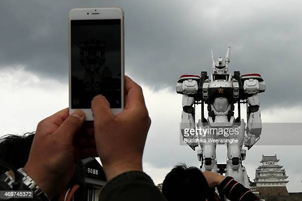 A fullsize model of the animation character Patlabor AV98 Ingram stands at front of the World Heritage Himeji castle man uses his smart phone and...