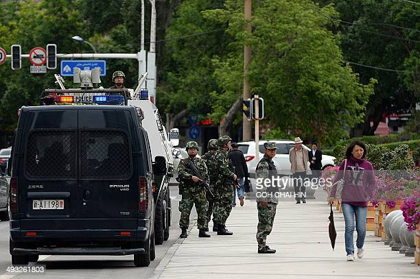 Fully armed Chinese paramilitary police officers stand guard along a street in Urumqi the capital of farwest China's Muslim Uighur homeland of...