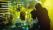 Fully Armed Special Anti-Narcotics Task Forces Soldier Arrests Two Clandestine Chemists Working in the Drug Producing Underground Laboratory. A lot of Drug Production Equipment is Lying around.