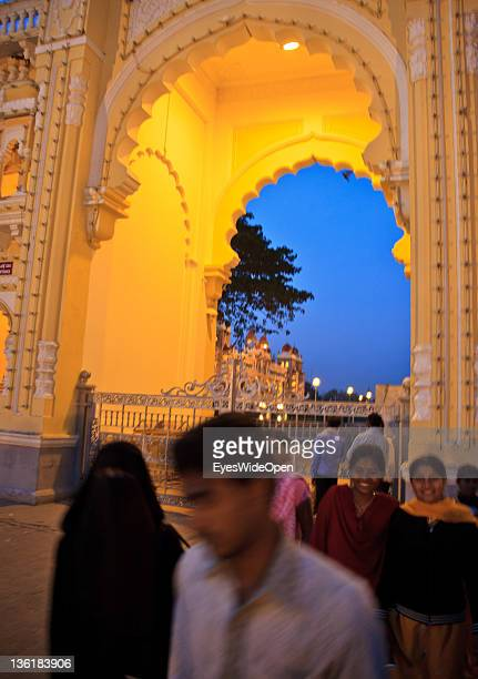 Fully covered muslim woman in a black Burka and Hindi women in sarees in front of he Mysore Maharaja Palace built in the indosaracenic style at...