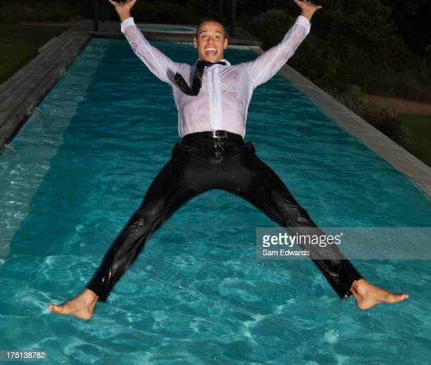 Entièrement habillé homme de sauter dans la piscine