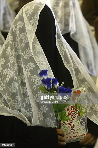 A fully veiled Iraqi Shiite bride takes part in a mass wedding in the holy city of Najaf 16 July 2006 550 couples were married today during a mass...
