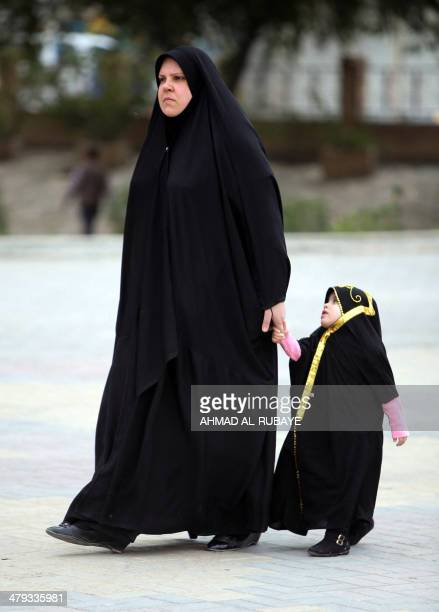 A fully veiled Iraqi woman walks with her equally fully veiled daughter in Baghdad on March 18 2014 A bill before Iraq's parliament that opponents...