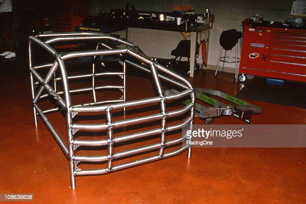 A fully welded roll cage sits on the floor of a NASCAR Cup shop ready to be installed in a car
