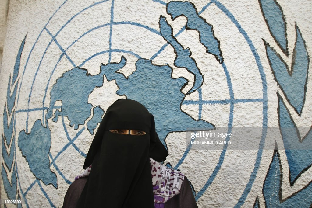A fully-veiled Palestinian woman stands outside the offices of the United Nations Relief and Works Agency (UNRWA) in Gaza city during a protest on April 8, 2013 to demand resumption of food deliveries to refugees, stopped last week after dozens of Gazans stormed a UN depot, demanding reinstatement of a monthly cash allowance to poor families which was halted from April 1 due to budget cuts. Gaza's Hamas rulers urged the UN on April 5 to reconsider its suspension of food aid for Palestinian refugees.