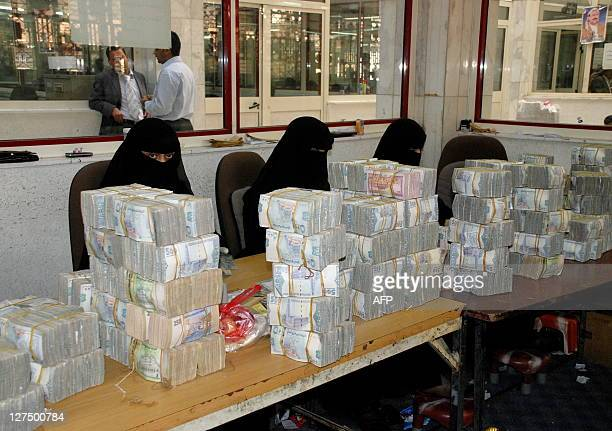 Fullyveiled Yemeni women count currency at the central bank in Sanaa on January 20 2010 The Yemeni riyal has lost 42 per cent against the dollar in...