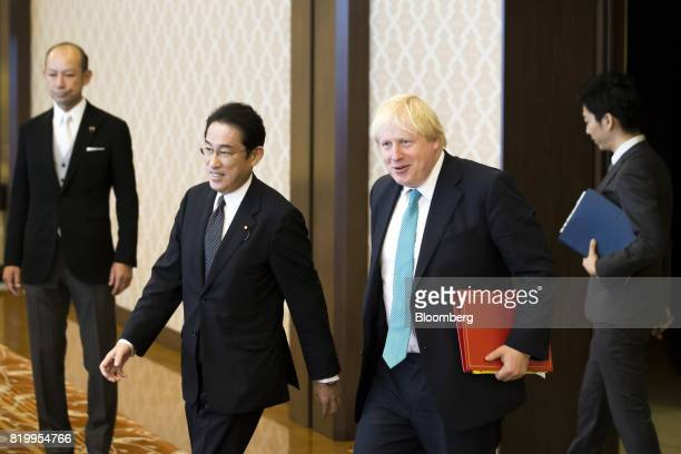 Fumio Kishida Japan's foreign minister center left and Boris Johnson UK foreign secretary center right arrive for a meeting in Tokyo Japan on Friday...