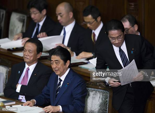 Fumio Kishida Japan's foreign minister right walks to the podium for his policy speech as Shinzo Abe prime minister front row center and Taro Also...