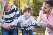 Father and mother teach their son to ride a bike