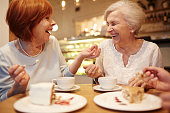 Two senior friendly females laughing during tea time