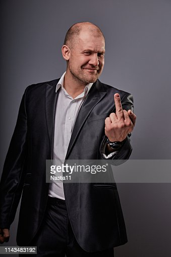 Fun comic bald business man in black suit showing the finger fuck sign on grey background. Closeup : Stock Photo