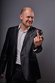 Fun comic bald business man in black suit showing the finger fuck sign on grey background. Closeup portrait