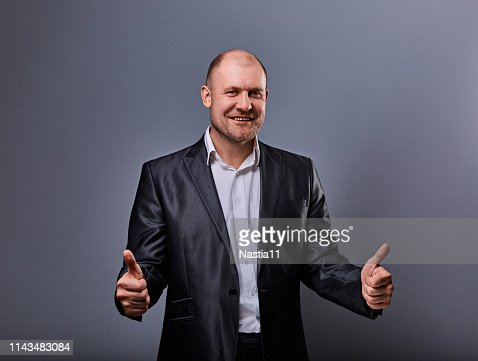 Fun comic bald business man in black suit showing the finger success thumb up sign on grey background. Closeup : Stock Photo
