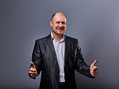 Fun comic bald business man in black suit showing the finger success thumb up sign on grey background. Closeup portrait