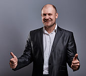Fun comic bald business man in black suit showing the finger success thumb up sign on grey background. Closeup contrast portrait