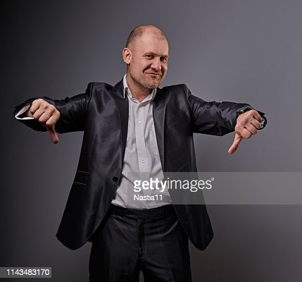 Fun comic bald business man in black suit showing the finger success thumb down sign on grey background. Closeup : Stock Photo