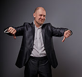 Fun comic bald business man in black suit showing the finger success thumb down sign on grey background. Closeup portrait
