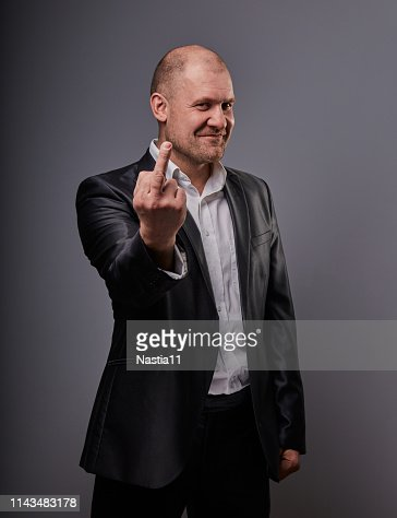 Fun comic smiling bald business man in black suit showing the finger fuck sign on grey background. Closeup : Stock Photo