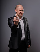 Fun comic smiling bald business man in black suit showing the finger fuck sign on grey background. Closeup portrait