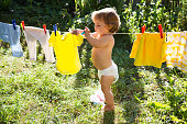 fun happy baby girl to wash clothes and laughs  in the meadow on a sunny summer day