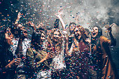 Group of beautiful young people throwing colorful confetti while dancing and looking happy