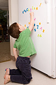 Preschool boy playing with magnetic letters on the kitchen refrigerator.