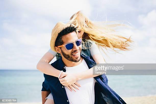 Fun piggyback against a cloudy blue sky
