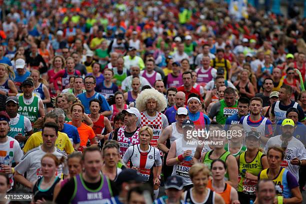 A fun runner wears a large white wig with other runners during the Virgin Money London Marathon on April 26 2015 in London England