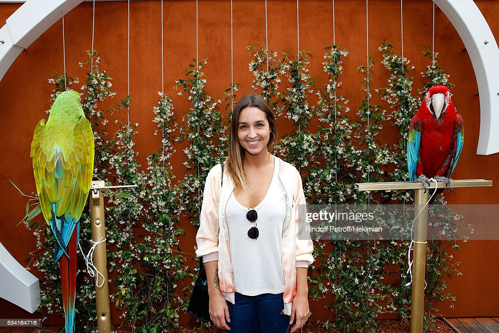 Funboard Champion Alice Arutkin standing between parrots Arthur (R) and Zoe (L) attend the 2016 French Tennis Open - Day Four at Roland Garros on May 25, 2016 in Paris, France.