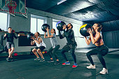 Functional fitness workout at the gym with medicine ball. The group of young people during training session. Fit athletic men and women at health club. Healthy lifestyle concept