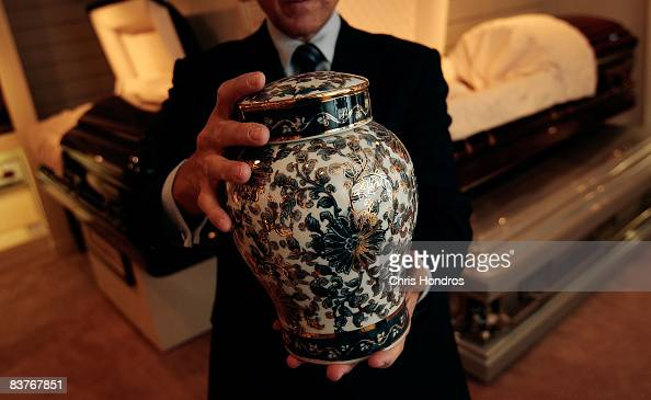 Funeral director Peter DeLuca owner of Greenwich Village Funeral Home holds a cremation urn in the showroom of his funeral parlor on November 20 2008...