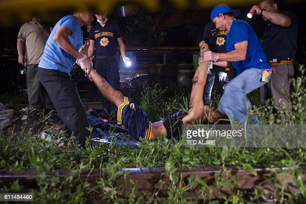 TOPSHOT Funeral parlor employess carry the the body of suspected drug pusher killed during a drug buybust operation by police along a rail line in...