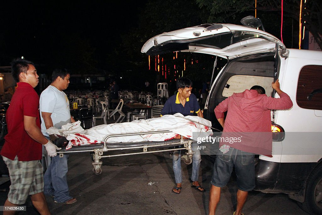 Funeral parlor workers carry a stretcher with a dead body into a vehicle after an improvised explosive device went off at a popular restaurant in Cagayan de Oro City, on the southern island of Mindanao on July 26, 2013. Six people were killed and more than 40 wounded in the Philippines when a bomb struck a restaurant filled with doctors after a national convention, police said on July 27. AFP PHOTO/ JB Deveza