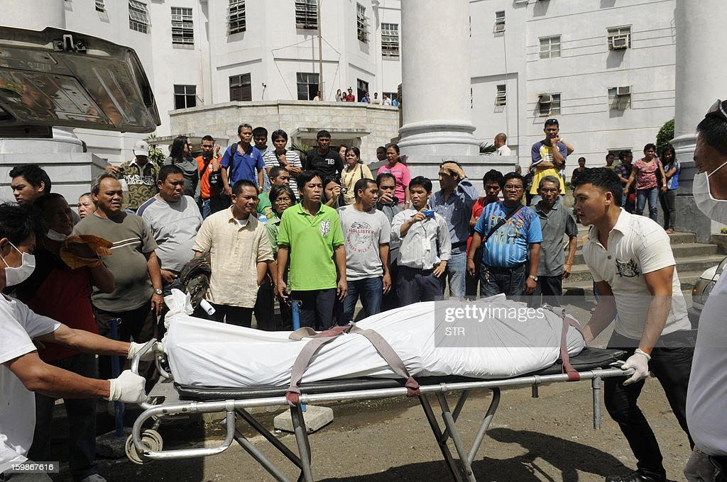 Funeral parlor workers push a stretcher carrying one of the two people shot dead by a Canadian national inside a court room, in Cebu City, central Philippines on January 22, 2013. A Canadian man shot dead two people including a lawyer in a Philippines courtroom on January 22, using a pistol he smuggled inside the court as he went on trial for petty mischief, police said.