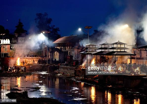 Funeral pyres burn during a mass cremation of earthquake victims on the banks of Bagmati river at the Pasupathinath temple in Kathmandu on April 29...