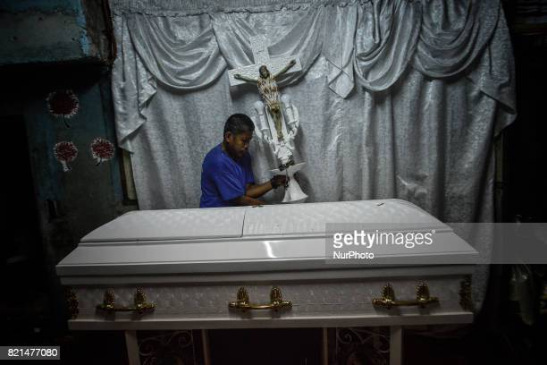 A funeral worker removes a crucifix prior to the funeral of Nino Maruso who was killed by police in what they say was a drug buybust operation in...