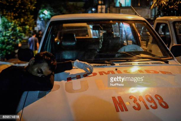 A funeral worker takes a nap on the bonnet of a police car near the scene where two men were killed by police in what they say was an antiillegal...