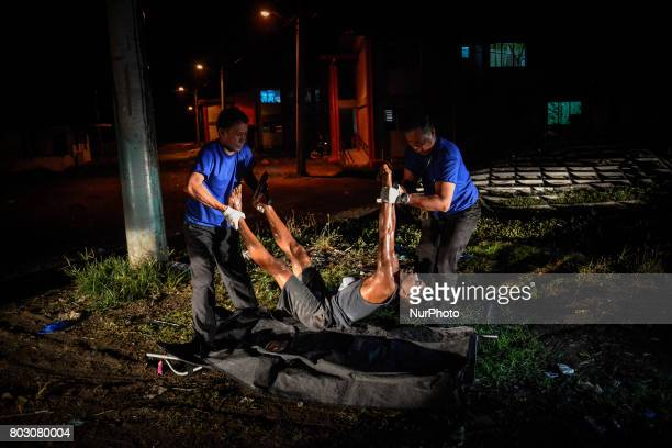 Funeral workers carry away the body of Edward Punzalan who was wanted for the murder of an elderly woman after he was shot dead by police in what...