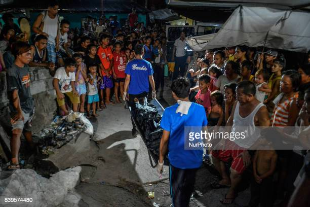 Funeral workers carry the body of one of three men killed during a police operation against illegal drugs in Caloocan Metro Manila Philippines August...