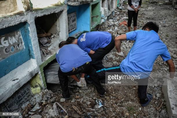 A funeral workers kicks into a tiny apartmentstyle tomb bodies of shooting victims unclaimed for months in Navotas north of Manila Philippines June...