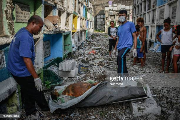 Funeral workers prepare to stuff into a tiny apartmentstyle tomb bodies of shooting victims unclaimed for months in Navotas north of Manila...