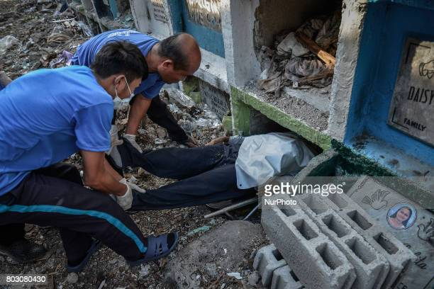Funeral workers stuff into a tiny apartmentstyle tomb bodies of shooting victims unclaimed for months in Navotas north of Manila Philippines June 19...