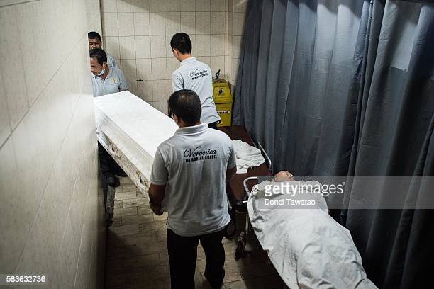 Funeral workers transport bodies of alleged drug dealers and victims of summary executions inside a funeral parlor on July 27 2016 in Manila...