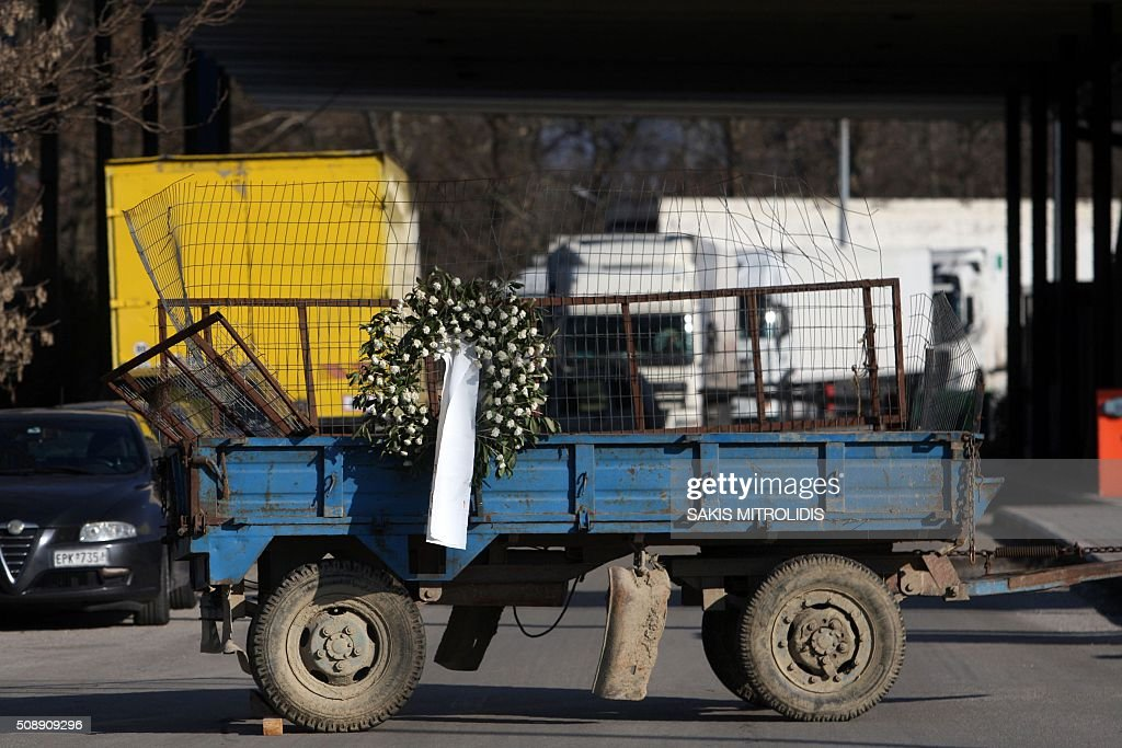 A funeral wreath is placed on a trailer at a closed customs post at the border crossing of Promachonas between Greece and Bulgaria, in northern Greece, as farmers set up a blockade of customs offices, shutting down the movement of trucks to and from Bulgaria on February 7, 2016. Greek farmers protesting against pension reforms heightened highway and border protests around the country, piling pressure on the leftist government of Prime Minister Alexis Tsipras. The mobilisation which began in mid-January has created tractor blockades at dozens of highway locations and key border crossings to Bulgaria and Turkey, which the farmers intermittently open for a few hours each day. / AFP / SAKIS MITROLIDIS
