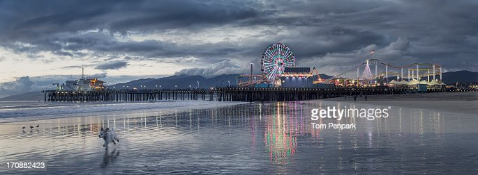 Funfair on Santa Monica pier reflecting in water, Santa Monica, California, USA