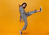 Full length of young woman in jumpsuit kicking over orange background. Funky female with raised leg looking at camera.