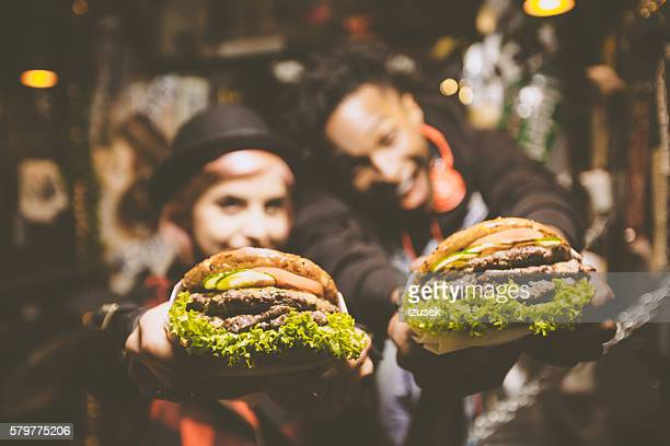 Funky friends in fast food restaurant, holding burgers