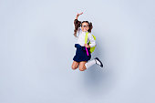 Funky nice cute genius positive cheerful lovely small little girl with curly pigtails in white formal blouse shirt, skirt, jumping, raising hand up, fooling, yellow bag. Isolated over grey background