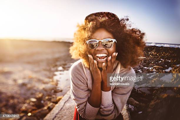 Fun-loving African American teenage hipster at the beach laughing