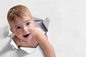 Funny background of a caucasian baby boy with blond hair coming out of a white paper broken. Horizontal composition. Front view.